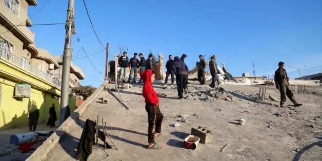 SULAYMANIYAH, IRAQ - NOVEMBER 13: People stand on a collapsed house, after a 7.3 magnitude earthquake...