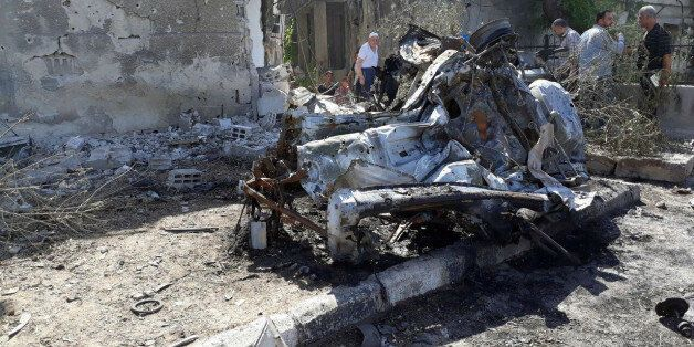 People inspect the site of a car bomb blast in Damascus in this handout picture posted on SANA on July...
