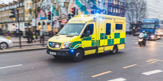 Emergency ambulance rushing on the street with emergency lights flashing in London city