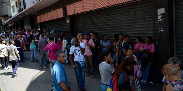 People queue outside a supermarket in Caracas to buy basic foodstuffs and household products on November...