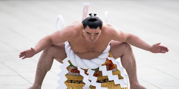 TOPSHOT - Mongolian-born sumo grand champion or 'yokozuna' Harumafuji performs a ring-entering ceremony...