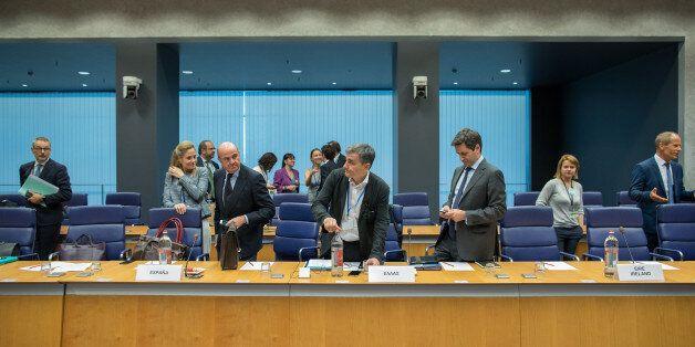 Euclid Tsakalotos, Greece's finance minister, center, prepares to take his seat as Luis de Guindos, Spain's...