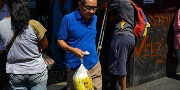 A man holds two bags of flour after queuing outside a supermarket in Caracas to buy basic foodstuffs...