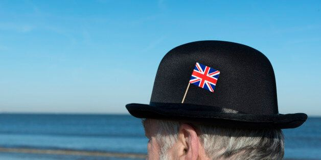 Englishman with bowler hat with union jack flag pinned on the hat on the beach overlooking the sea and...