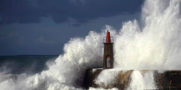 Waves crash against a lighthouse in Viavelez, northern Spain, January 21, 2015. REUTERS/Eloy Alonso (SPAIN...