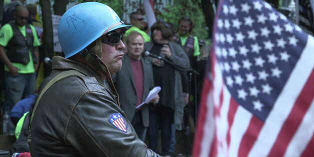 A rally attendee listens to an alt-right speaker during a free speech rally at Terry Schrunk Plaza in...