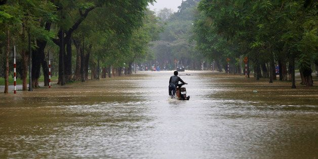 A man pushes his motorcycle along flooded road after typhoon Damrey hits Vietnam in Hue city, Vietnam...
