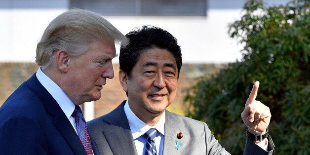 U.S. President Donald Trump (L) is welcomed by Japan's Prime Minister Shinzo Abe upon his arrival at...