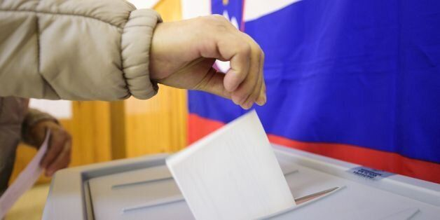 A slovenian citizen casts her ballot for the first round of the presidential election at a polling station...