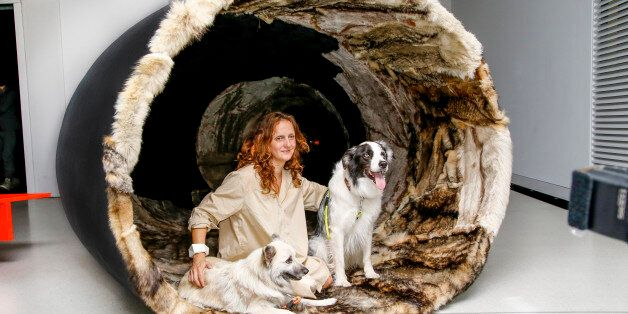 BERLIN, GERMANY - JULY 21: Artist Maja Smrekar and her dogs sit in her wolf coat tunnel 'K-9_topology:...