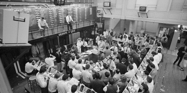 Traders keep an eye on the latest figures at the end of a difficult week at the Paris Stock Exchange....