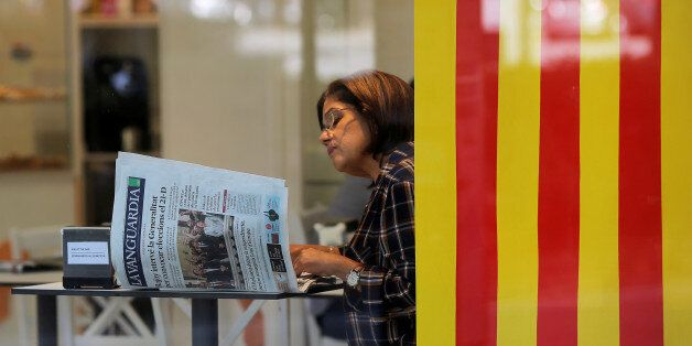A woman reads a newspaper next to a Catalan flag at a coffee shop the day after the Catalan regional...