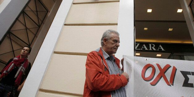 A protester from the retail sector federation holds a banner outside a store during a rally to demonstrate...