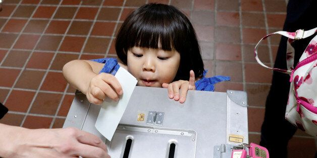 A girl casts her father's ballot for a national election at a polling station in Tokyo, Japan October...
