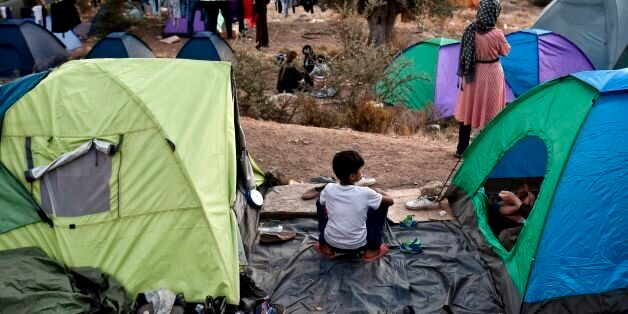 Recently arrived refugees sit in a makeshift tent camp near the overcrowded hotspot on the Greek eastern...