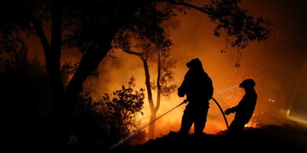 Firefighters work to extinguish flames from a forest fire in Cabanoes near Lousa, Portugal, October 16,...