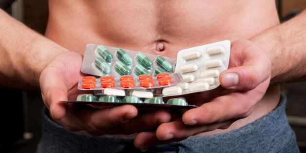 Muscle man holding bunch of blisters with colored vitamin
