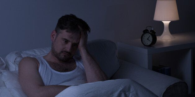Man suffering from sleeplessness sitting in the