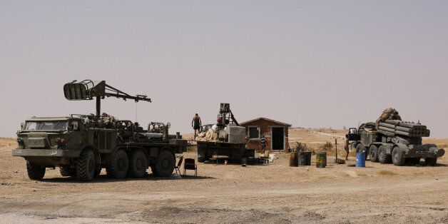 A man stands near military vehicles that belong to the Syrian army in Deir al-Zor, Syria September 21,...