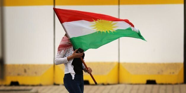 An Iraqi Kurd marches with a Kurdish flag during a protest in support of the Iraqi Kurdish leader, in...