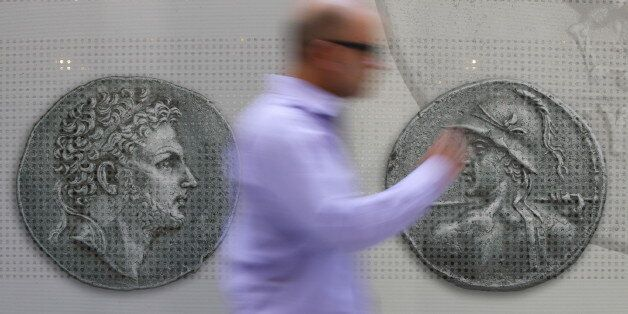A man walks past pictures of ancient coins in central Athens, Greece, July 13, 2015. Euro zone leaders...