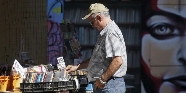 A man looks at used DVDs at a store at Monastiraki area in central Athens, Greece, July 7, 2015. Greece...