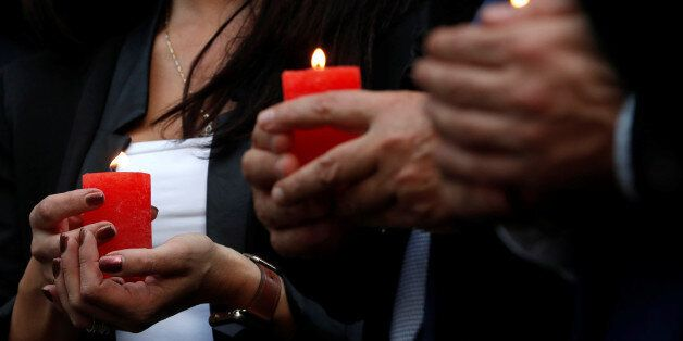 People hold candles as they gather for a candlelight vigil in memory of Malta's journalist Daphne Caruana...