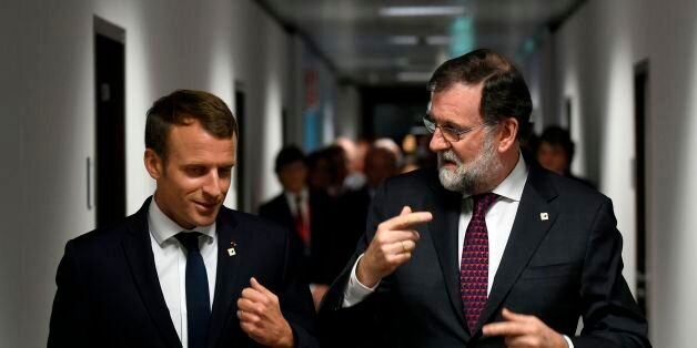 French President Emmanuel Macron (L) speaks with Spanish Prime Minister Mariano Rajoy (R) on their way...