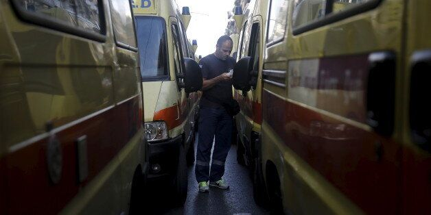 A rescuer of the Greek National Centre of First Aid walks among ambulances during a protest outside the...