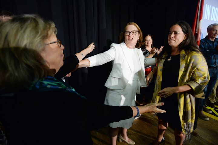 Independent candidates Jody Wilson-Raybould, right, and Jane Philpott, centre, and Green Party Leader Elizabeth May hug in Vancouver on Sept. 18, 2019.
