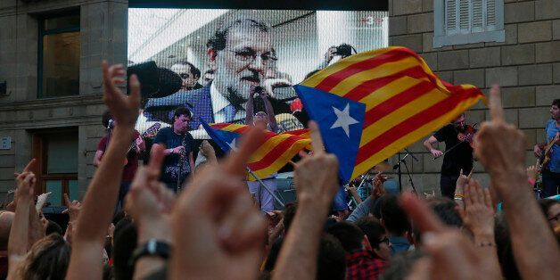 People look at a giant screen broadcasting Spain's Prime Minister Mariano Rajoy during a press statement...