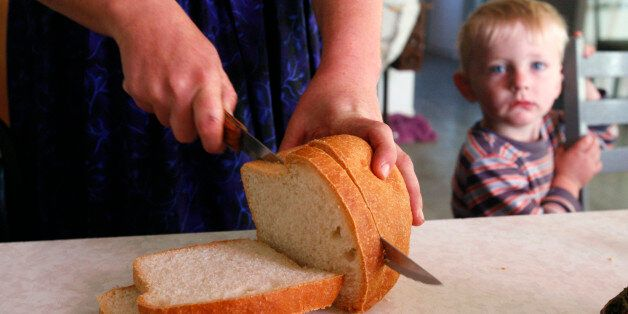 A woman from a Mennonite community slices bread for breakfast as her son looks on at their home in Cuauhtemoc November 9, 2012.  More than a century after Mennonite farmers left Russia for North America in search of new lands and religious freedom, hundreds of their descendants in Mexico are thinking about completing the circle. Shortage of farmland, drought and conflict with rivals have made some Mennonites in northern Mexico wonder if the best way of providing for their families is to go back to the plains of eastern Europe their ancestors left in the 19th century.  Picture taken November 9, 2012. To match Feature MEXICO-MENNONITES/      REUTERS/Jose Luis Gonzalez (MEXICO - Tags: FOOD SOCIETY RELIGION)