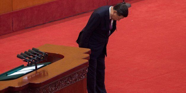 China's President Xi Jinping bows to delegates after delivering a speech at the opening session of the...