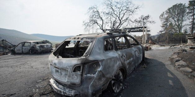 The remains of a burnt vehicle in front of a house in Sonoma County, California after the recent devastating...
