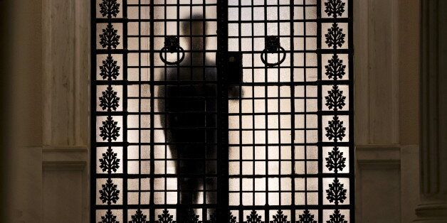 A man is silhouetted inside the Maximos Mansion as Greek Prime Minister Alexis Tsipras (not pictured)...