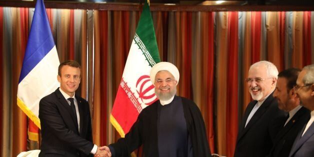 France's President Emmanuel Macron (L) shakes hands with his Iranian counterpart Hassan Rouhani as Iran's...