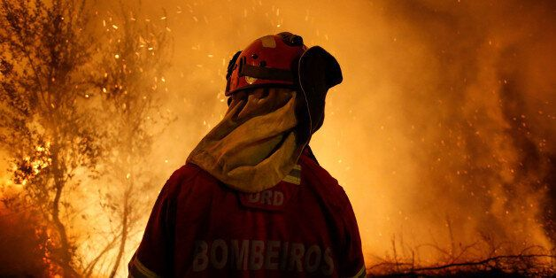 A firefighter is seen near flames from a forest fire in Cabanoes, near Lousa, Portugal, October 16, 2017....