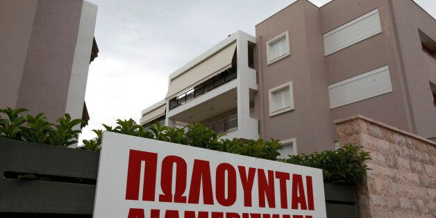 A sign advertises 'apartments for sale,' outside a new luxury housing development in the Glyka Nera suburb...