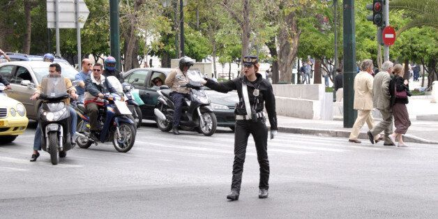Athens, Greece - May 5th, 2005: A female traffic cop in Athens, Greece beckons oncoming traffic while...