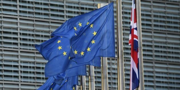 A Union Jack (R) hangs down next to European Union flags fluttering in front of the European Commission...