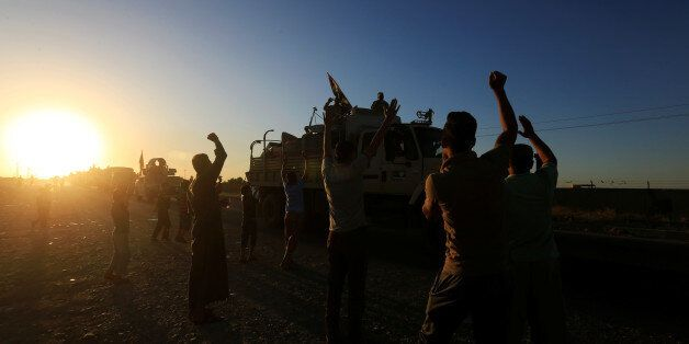 People gather on the road as they welcome Iraqi security forces members who continue to advance in military...