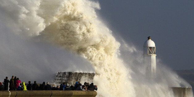 TOPSHOT - Huge waves strike the harbour wall and lighthouse at Porthcawl, south Wales, on October 16,...