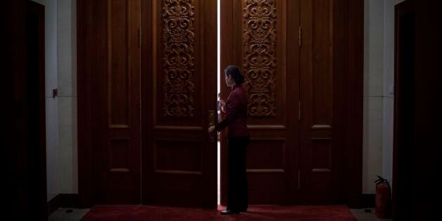 A hostess closes the door of a meeting room at the Great Hall of the People during the Communist Party's...