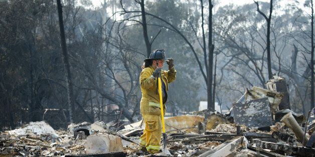 SANTA ROSA, CA - OCTOBER 13: A firefighter pauses for a moment while looking through the rubble of a...