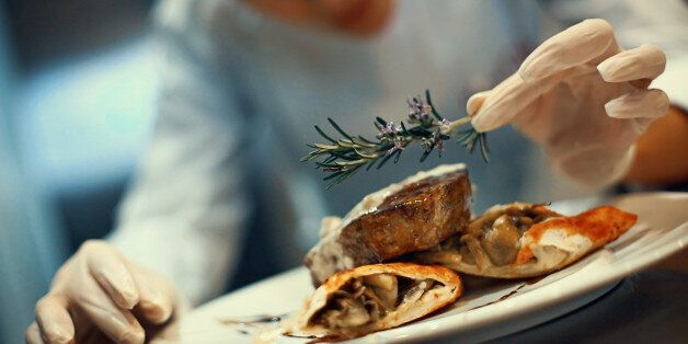 Closeup tilt of blurry female chef placing rosemary on a steak meal before serving. She's using protective...