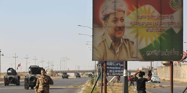A banner bearing a portrait of Kurdish regional president Massoud Barzani is seen as Iraqi forces advance...