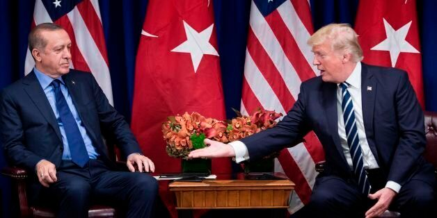 US President Donald Trump reaches to shake Turkey's President Recep Tayyip Erdogan's hand before a meeting...