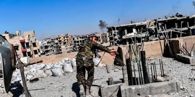 Members of the Syrian Democratic Forces (SDF), backed by US special forces, walk on a building near Raqa's...