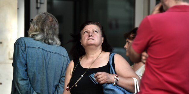 A woman holding a bank card looks up as people queue outside a bank to withdraw cash from an ATM in Athens...