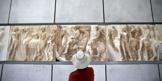 A man looks at exhibits at the Parthenon hall of the Acropolis museum in Athens May 18, 2015. Museums...